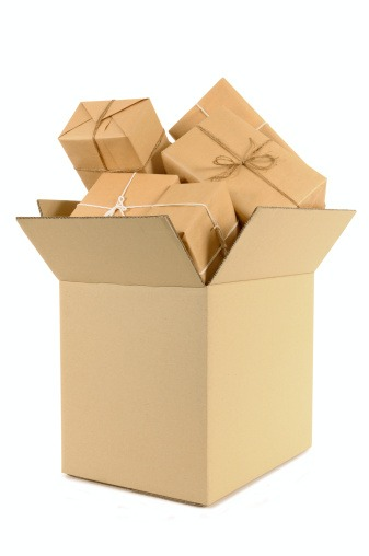 Cardboard box overflowing with numerous brown paper packages.